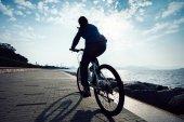 Fotografie silueta cyklista jízdní kolo v silnici pobřeží sunrise