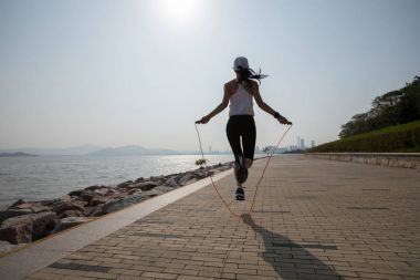 sporty young fitness woman jumping rope on coast trail