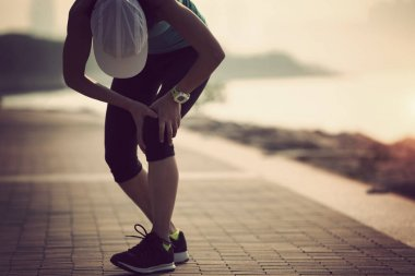 female runner with injured knee after morning exercise
