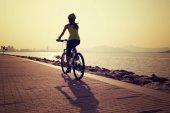 Žena cyklista jízdní horské kolo na moře