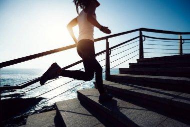 sporty female jogger running upstairs on seaside during sunrise