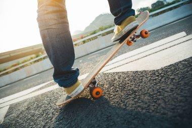 Cropped image of skateboarder skateboarding on city street