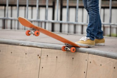 Cropped image of kateboarder practicing on skatepark ramp
