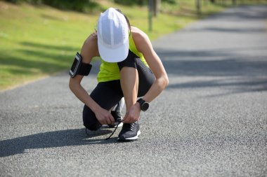young fitness woman runner tying shoelace on the forest trail