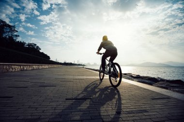 cyclist riding bike in the sunrise coast path