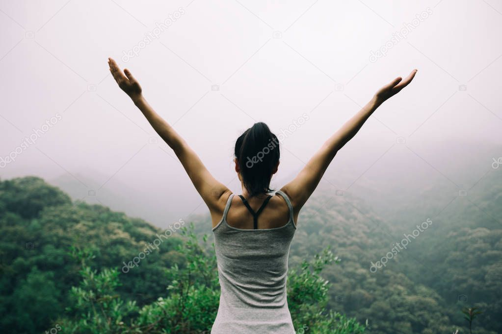 Young woman with outstretched arms enjoying the view on morning mountain valley