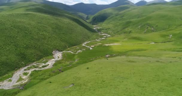 Aerial view over green meadows and rivers in beautiful China mountains landscape