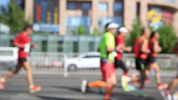 Blurred footage of female and male marathon runners jogging on race on city road, Shenzhen, China.