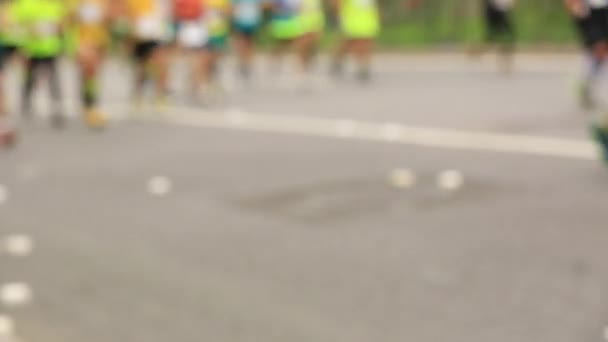 Blurred footage of marathon runners running race on city road