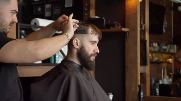 Barber cutting hair of male client