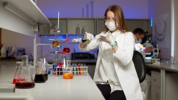 Junge Wissenschaftlerin mischt farbige Flüssigkeiten