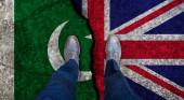 Obchodník stojí na popraskané vlajce Uka a Pákistánu. Politický koncept