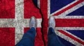 Obchodník stojí na popraskané vlajce Velké Británie a Dánska. Politický koncept