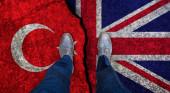 Obchodník stojí na popraskané vlajce Velké Británie a Turecka. Politický koncept