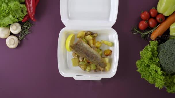 Balení jídla s sebou v polystyrénové krabici. Čerstvé balení s rybami a bramborami