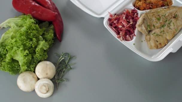 Balení jídla s sebou v polystyrénové krabici. Čerstvé jídlo s kuřecími prsíčky, rýží se zeleninou a salátem