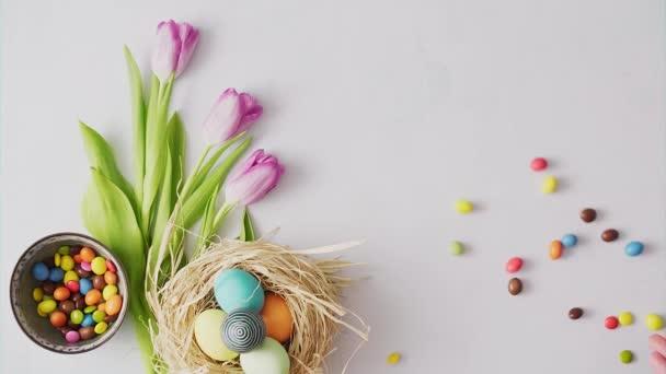 Bonbons rollen auf einem Tisch, der mit bunten Ostereiern auf hellem Hintergrund dekoriert ist. Osterfestdekoration, Osterkonzept Hintergrund.