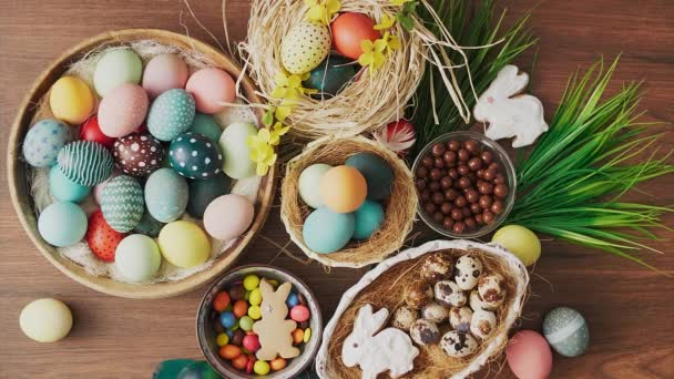 Feathers falling on colorful Easter eggs in nest and spring flowers on wooden table. Easter holiday decorations, Easter concept background.