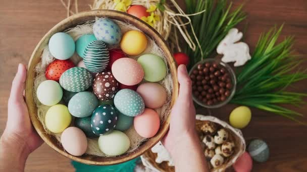 Hands holding basket full of colorful Easter eggs in front of decoration on wooden table. Easter holiday decorations, Easter concept background.