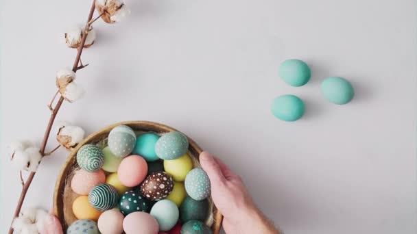 Ruce zvedání koše s barevnými velikonočními vejci na jasném pozadí. Velikonoční prázdninové dekorace, Velikonoční koncept pozadí.