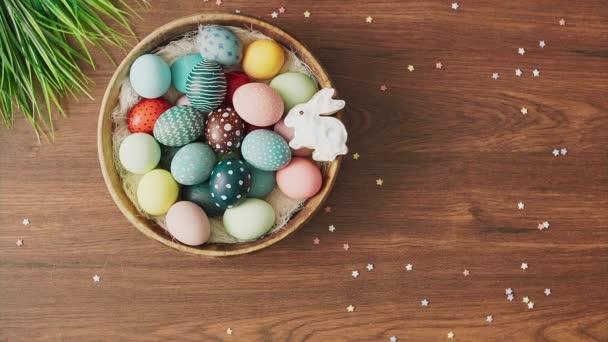 Ruce položí hnízdo plné barevných velikonočních vajíček a tulipánů na zdobený dřevěný stůl. Velikonoční prázdninové dekorace, Velikonoční koncept pozadí.