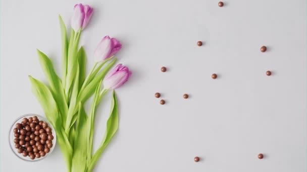 Hände legen Nester mit bunten Ostereiern auf hellem Hintergrund ab. Osterfestdekoration, Osterkonzept Hintergrund.