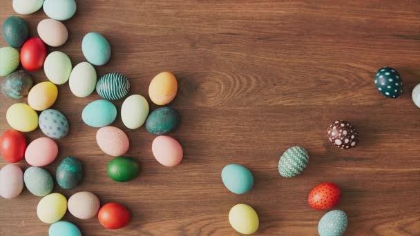 Színes húsvéti tojás gurul a fa asztalon. Húsvéti ünnepi dekorációk, húsvéti koncepció háttér.