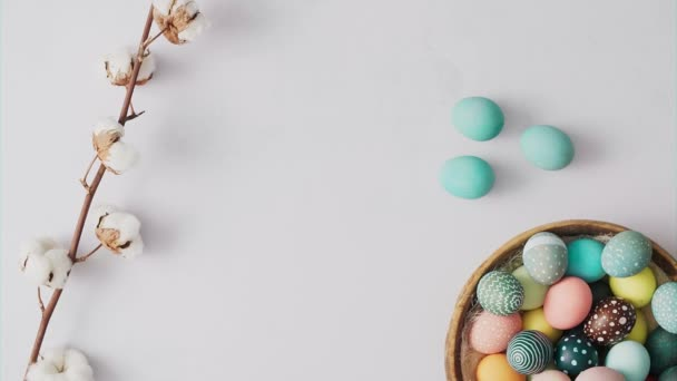 Hands picking up basket with Colorful Easter eggs on bright background. Easter holiday decorations , Easter concept background.