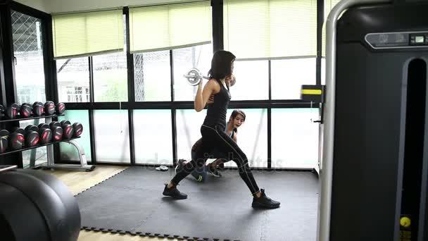 Žena a osobní trenér dělá výpad s činka a protahuje svaly v tělocvičně