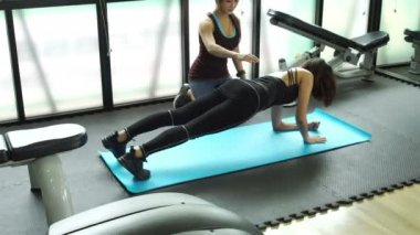 Trainer and woman at gym push up push-up workout exercise