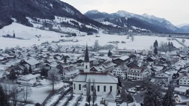 Luftaufnahme der kleinen gemütlichen deutschen Stadt am Fuße des Berges bei Sonnenaufgang in einer Wintersaison, Halblech Stadt, Deutschland, Bayern, Zweige der Bäume sind mit Raureif bedeckt, sonniges Wetter