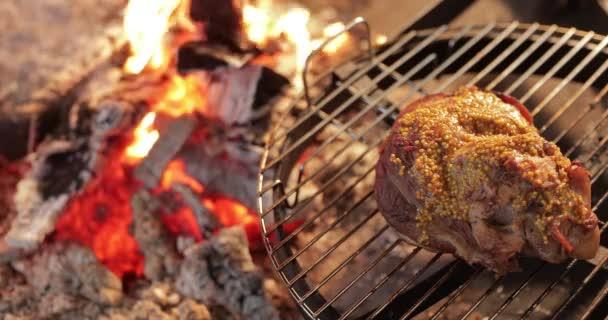 Velký kus nakládaného masa leží na kulatém grilu, v blízkosti velkého nahého ohně, maso je naloženo hořčicí, červeným uhlím, kouřem, palivem, ruce kuchaře připravit uhlí, ultra hd kvalita, 4k video