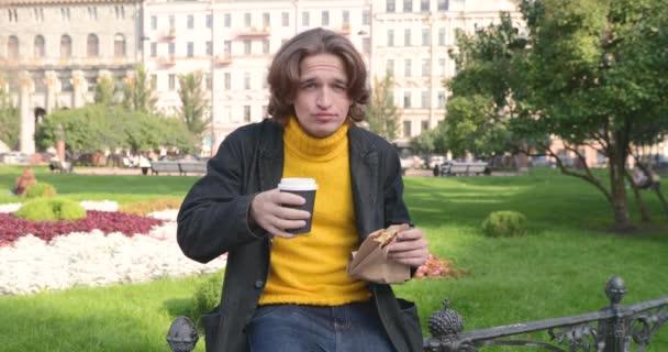 A fiatalember kávét iszik és édes süteményt eszik a parkban, mosolyog, sárga pulcsiban és fekete esőkabátban vagy zakóban van, farmer nadrágban, virágban és zöld fűben a háttérben, napsütéses napon.