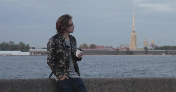 The handsome men is waiting someone, drinks coffee and looks in phone, he is dressed in a military jacket and jeans, Peter and Paul fortress is on background