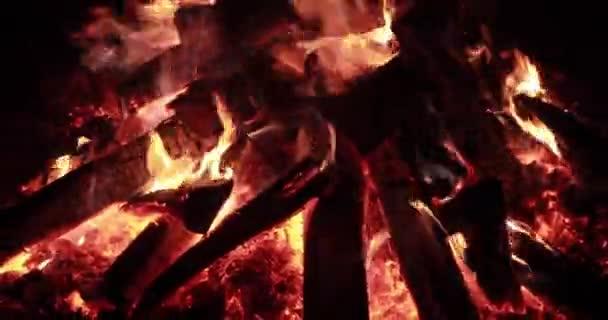 Velký oheň s palivem v noci, táborák hořící v noci, jiskry, plameny ohně, je spousta červených dřevěných uhlíků, krb, zpomalené video bez zvuku, páry a kouře