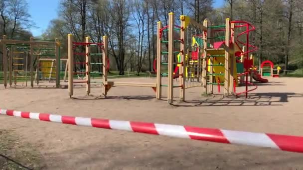 A játszóteret egy piros-fehér szalaggal kerítették be a parkban a karantén alatt a koronavírus világjárvány idején, nincsenek gyerekek a helyszínen, a belépés le van zárva.