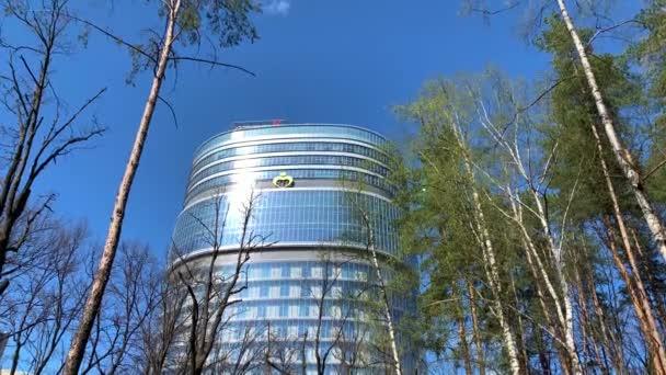 Russland, St.Petersburg, 07. Mai 2020: Das Nationale Medizinische Forschungszentrum VA Almazov, Blick durch Äste von Bäumen mit grünen Blättern, blauer Himmel im Hintergrund, Sonnenreflexe auf Glas der Fassade