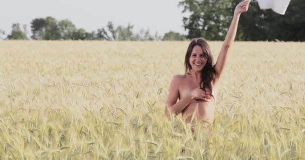 Francie, Provence, The beautiful young girl dances in the field of wheat at sunset, swings a white t-shirt, happy girl with long hair, green trees on background