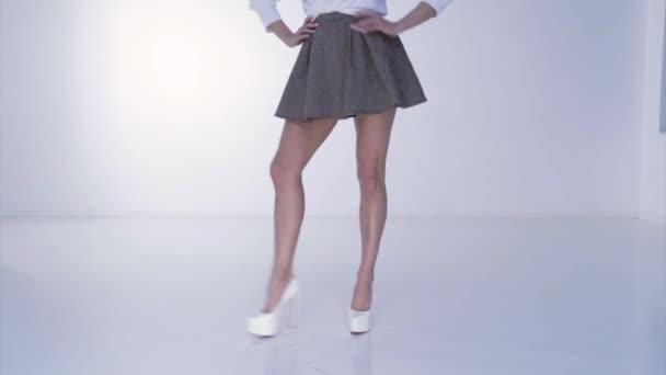 Lange Beine einer jungen schönen Frau auf weißem High Heel, rote Schuhsohle, kurzer Rock, Füße auf weißem Hintergrund, tanzt, kokettiert, der kurze Rock wird gedreht, die Sportfigur
