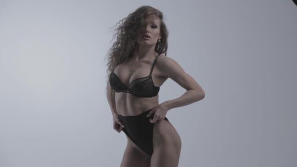A fiatal gyönyörű nő göndör haj pózol, rángatózik és flörtöl a kamera előtt, szexuális fehérnemű fekete színű, fehér háttér, táncol, ő coquets, Különböző érzelmek az arcon