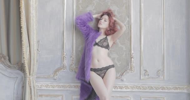 Mladá krásná dívka s dlouhými kudrnatými zrzavými vlasy ve fialovém kožichu a černém spodním prádle pózuje, flirtuje a dotýká se vlasů, Krásné boky, sexuální postava, skleslý vzhled, zrzavé vlasy