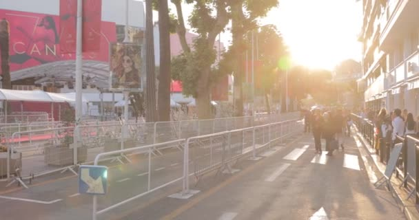 France, Cannes, 27 May 2017: Streets of Cannes at the cinema Cannes Film festival, branches palms at sunset, embankment, ladies and gentlemen in evening dresses, crowded cafes, entertainments