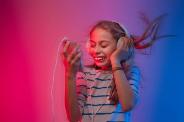 Girl with smartphone and headphones listens to music