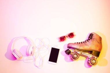Roller skates, smartphone, headphones and sunglasses