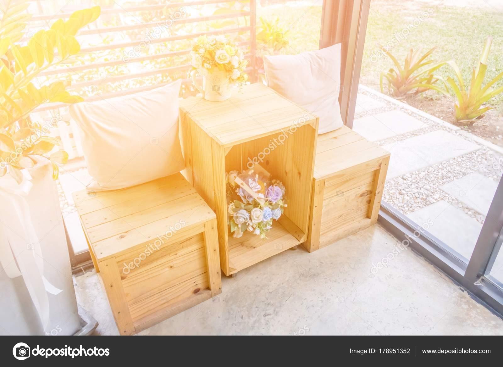 Due cuscini sullo scrittorio di legno con legno sgabello e vasi di