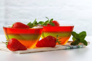 On a white table, fruit jelly with strawberries