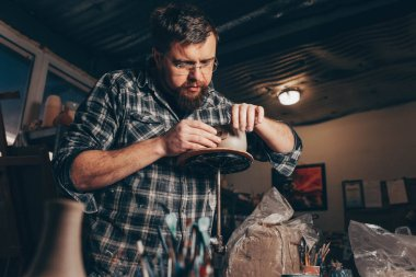 Bearded man works in a pottery workshop, concentrating on the process of creating a clay cup
