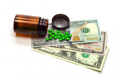 Medicines and various cash dollars. Cash and pills. Medicine in trade, isolated on a white background.