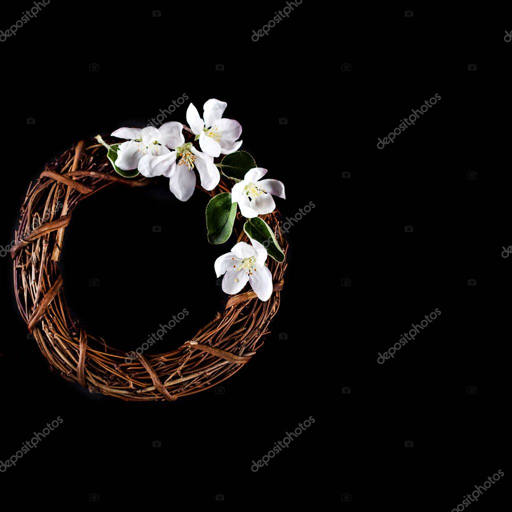 Wreath with spring flowers on a dark wooden background.