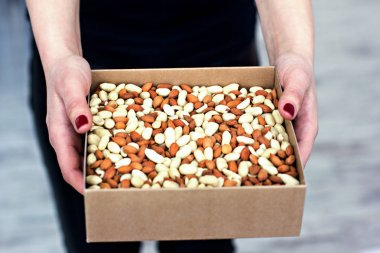 Female hands hold a box of nuts and dried fruits.